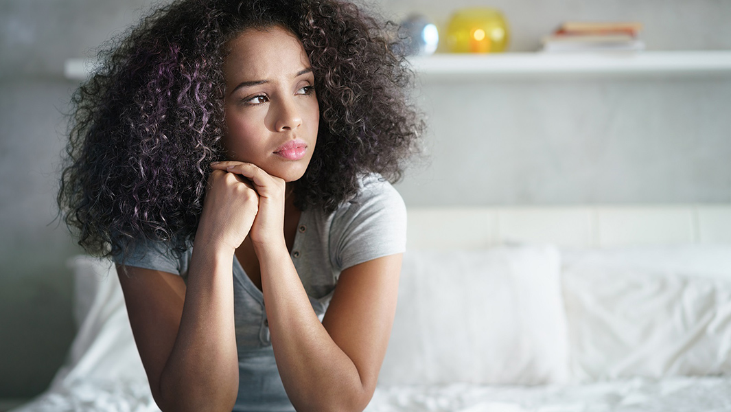 Concerned woman sitting on bed