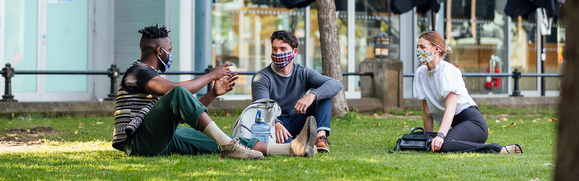 Group of adults wearing masks sit outside