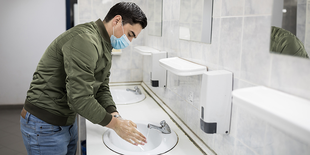 Man washes his hands at a sink