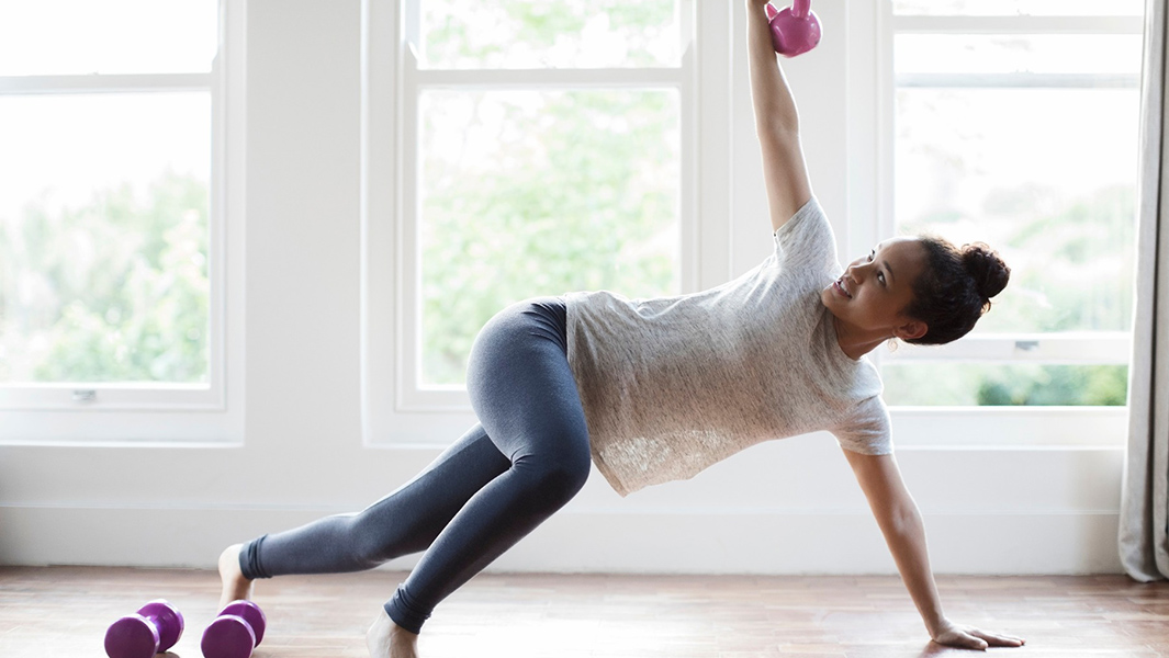 Woman exercising with weights in her home