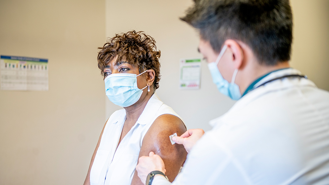 Doctor places band-aid on woman's arm after receiving the vaccine