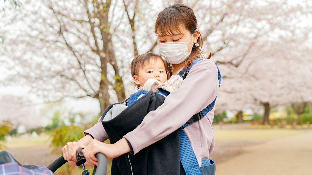 Masked Woman Walking with Her Baby During COVID-19 Pandemic